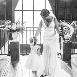 Bride poses with flower girl following her ceremony at The Diary Barn coordinated by Magnificent Moments Weddings