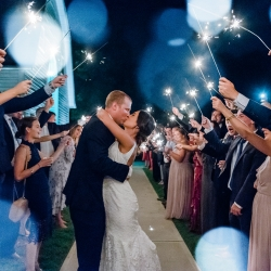 Bride and groom exit during a sparkler sendoff coordinated by Magnificent Moments Weddings at The Diary Barn
