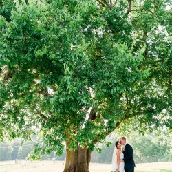 Bride and groom pose under large tree before their wedding ceremony at The Diary Barn in Fort Mill. South Carolina