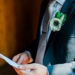 Detail shot of groom reading a letter showing of his boutineer by Wild Petal Studios, the moment is captured by Ashley Sue Photography