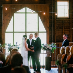 Bride and groom exchange vows in front of a stunning window accented by vintage Edison lights during their ceremony at The Dairy Barn in Fort Mill, South Carolina