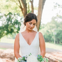 Bride holds amazing bridal bouquet by Wild Petal Studio with large white flowers and accents of blue