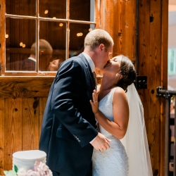 Bride and groom share a kiss during their cake cutting of a beautiful publix cake during their wedding at The Dairy Barn