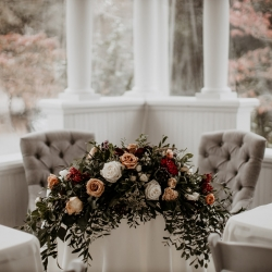 Stunning sweetheart table centerpiece by Heatherly Event Design featured lush fall colors for a wedding at Ritchie Hill