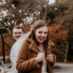Bride bundles up as she gets ready to walk down the aisle during her fall wedding coordinated by Magnificent Moments Weddings