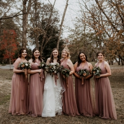 Avonne Photography captures a bride and her bridesmaids wearing blush pink gowns and holding bouquets created by Heatherly Event Designs