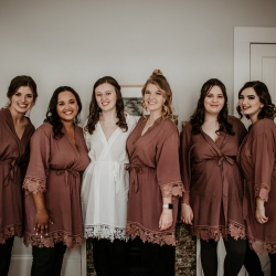 Bride and her bridesmaids pose in matching robes as they prepare for their fall wedding coordinated by Magnificent Moments Weddings