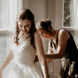 Bride puts on her gown as she prepares to walk down the aisle during her fall wedding at Ritchie Hill