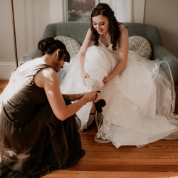 Avonne Photography captures a bride putting on her shoes as she prepares to walk down the aisle