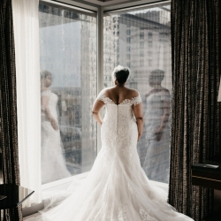 Bride shows off the stunning details of her wedding dress by Poffie Girls before her uptown Charlotte wedding