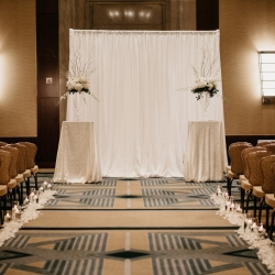 Crisp white alter marked by draping and large centerpieces for a wedding at The Ritz Carlton