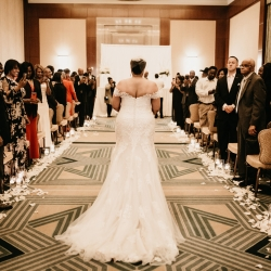 Avonne Photography captures a bride walking down the aisle to meet her groom during their ceremony planned by Magnificent Moments Weddings