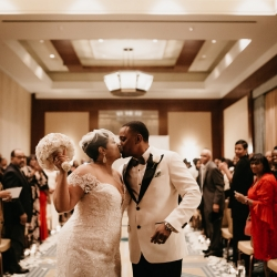 Bride and groom share a kiss after exchanging vows during their wedding ceremony planned by Magnificent Moments Weddings