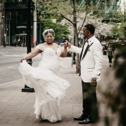 Bride and groom walk the streets of Uptown Charlotte during their spring wedding at The Ritz Carlton