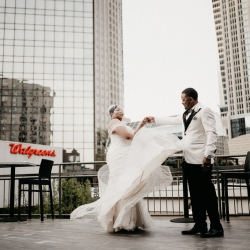 Bride twirls his groom among Charlotte's skyscrapers during their spring wedding planned by Magnificent Moments Weddings