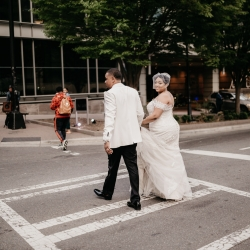 Bride and groom walk hand in hand in the streets of Uptown Charlotte during their spring wedding captured by Avonne Photography
