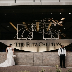 Bride and groom pose in front of the Ritz Carlton the location of their spring wedding