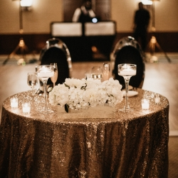 Stunning sweetheart table features gold sparkle linen from CLux and white floral centerpiece created by Partyblooms