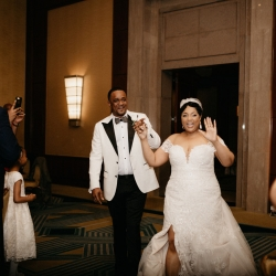 Bride and groom are all smiles as they walk into their reception space at the The Ritz Carlton which was designed by Magnificent Moments Weddings