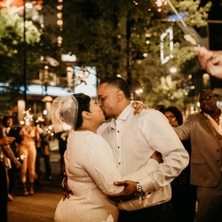 Bride and groom exchange a kiss during a sparkler send off after their wedding at the Ritz Carlton in Uptown Charlotte