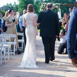 The bride is escorted down the aisle during her spring ceremony at The Ballantyne Hotel