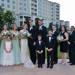 The bride and groom pose with their bridal party on the grounds of The Ballantyne Hotel