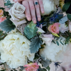 The soft spring colors of the brides bouquet created by Jimmy Blooms are the perfect backdrop to show off their sweet wedding rings