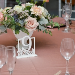 Jimmy Blooms created soft floral centerpieces in white vases for a spring wedding