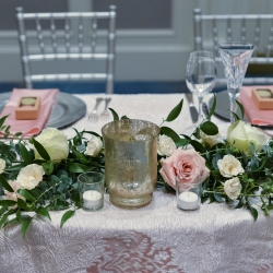Greenery accents and soft pink roses are the perfect touch to a sweetheart table at The Ballantyne Hotel