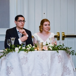 Bride and groom are all smiles as their friends and family toast them during their wedding reception coordinated by Magnificent Moments Weddings