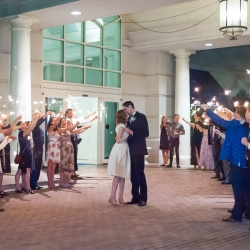 Bride and groom share a kiss during a grande exit coordinated by Magnificent Moments Weddings during a spring wedding at The Ballantyne Hotel