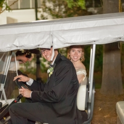 Bride and groom depart in a golf cart to explore their grounds of The Ballantyne Hotel on their wedding day coordinated by Magnificent Moments Weddings