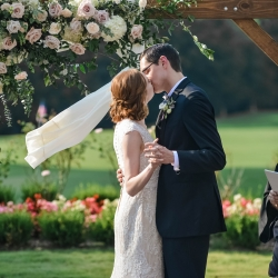 Bride and groom share a kiss at their ceremony presided over by Reverend Rebecca Nagy at The Ballantyne Hotel