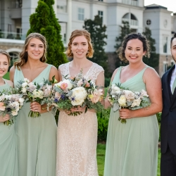 Bride poses with her bridal party wearing soft green dresses and holding a floral mix bouquet created by Jimmy Blooms