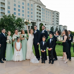 Bridal party poses in front of the Ballantyne Hotel before a spring wedding coordinated by Magnificent Moments Weddings