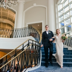 Bride and groom are introduced in to their wedding down a stunning spiral staircase at The Ballantyne Hotel