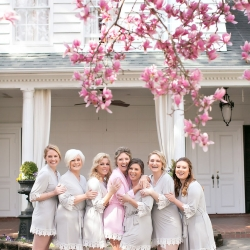 Bride and bridesmaids pose in matching robes as they prepare for their Charlotte wedding coordinated by Magnificent Moments Weddings