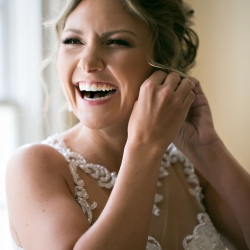 Bride puts on her earrings after hair and makeup by Be Pretty is finished for her Uptown Charlotte wedding
