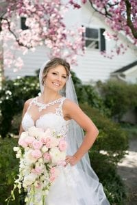 Bride poses holding a stunning bridal bouquet crated by The Blossom Shop before her wedding ceremony at Belk Chapel