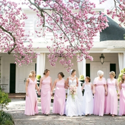 Bride poses with her bridesmaids all wear soft pink dresses