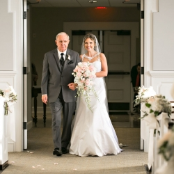 Old South Studios captures a bride being escorted down the aisle by her father during her wedding ceremony at Belk Chapel