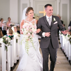 Bride and groom smile at guests as they leave their wedding ceremony at Belk Chapel captured by Old South Studios