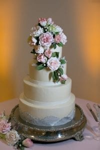 Kathy Allen Fine Cakes creates a stunning for tier white cake with floral accents for a wedding reception at The Levine Museum of the New South