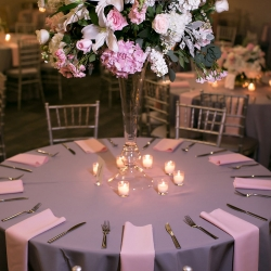 Gray table cloths and pink napkins show off large centerpieces by The Blossom Shop featuring a variety of pink and white flowers
