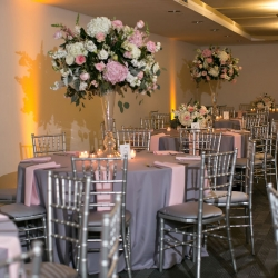 Stunning floral centerpieces created by The Blossom Shop featured white and pink flowers in tall vases for a wedding reception at The Levine Museum of the New South