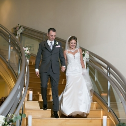 Bride ans groom descend the stairs into their reception at the Levine Museum of the New South coordinated by Magnificent Moments Weddings