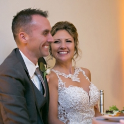 Bride and groom smile during their wedding reception in Uptown North Carolina coordinated by Magnificent Moments Weddings