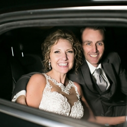 Bride and groom depart their Uptown Charlotte wedding in transportation provided by Silver Fox