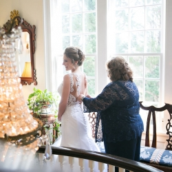 Brides mother helps button up her dress as she prepares for her wedding ceremony at Belk Chapel captured by Old South Studios
