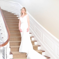 Bride standing on stairs getting ready at Forest Hill Church in Charlotte